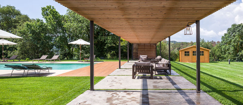 Extensa zona de jardín con césped y  piscina aigua salada